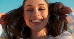 Συναισθηματικό πορτρέτο της πανέμορφης νέας γυναίκας με τη φυσική σύνθεση και το μεγάλο γοητευτικό χαμόγελο που εξετάζει τη κάμερ φιλμ μικρού μήκους