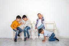 Συναισθηματικό στούντιο που πυροβολείται των παιδιών, κοριτσιών και τριών αγοριών που κάθονται στην αναμονή καρεκλών Τα παλαιότερ στοκ εικόνα