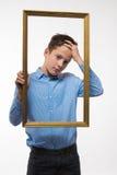 Συναισθηματικό brunette αγοριών σε ένα μπλε πουκάμισο με ένα πλαίσιο εικόνων στα χέρια Στοκ εικόνες με δικαίωμα ελεύθερης χρήσης