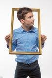 Συναισθηματικό brunette αγοριών σε ένα μπλε πουκάμισο με ένα πλαίσιο εικόνων στα χέρια Στοκ εικόνα με δικαίωμα ελεύθερης χρήσης
