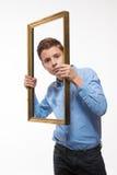Συναισθηματικό brunette αγοριών σε ένα μπλε πουκάμισο με ένα πλαίσιο εικόνων στα χέρια Στοκ φωτογραφία με δικαίωμα ελεύθερης χρήσης