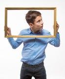 Συναισθηματικό brunette αγοριών σε ένα μπλε πουκάμισο με ένα πλαίσιο εικόνων στα χέρια Στοκ φωτογραφίες με δικαίωμα ελεύθερης χρήσης