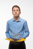 Συναισθηματικό brunette αγοριών σε ένα μπλε πουκάμισο με το κίτρινο φύλλο του εγγράφου για τις σημειώσεις Στοκ Εικόνες