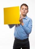 Συναισθηματικό brunette αγοριών σε ένα μπλε πουκάμισο με το κίτρινο φύλλο του εγγράφου για τις σημειώσεις Στοκ εικόνες με δικαίωμα ελεύθερης χρήσης
