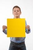 Συναισθηματικό brunette αγοριών σε ένα μπλε πουκάμισο με το κίτρινο φύλλο του εγγράφου για τις σημειώσεις Στοκ Φωτογραφία