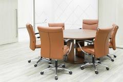 Συνανμένος ξύλινος πίνακας και καφετιές καρέκλες στην αίθουσα συνεδριάσεων στοκ φωτογραφία με δικαίωμα ελεύθερης χρήσης
