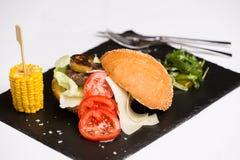 Συναντήστε burger που εξυπηρετείται με το τυρί και τα λαχανικά Στοκ Εικόνα