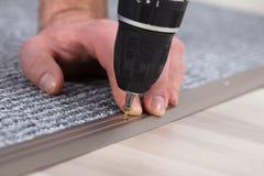 Συναρμολογητής ταπήτων που εγκαθιστά τον τάπητα με το ασύρματο κατσαβίδι στοκ φωτογραφία