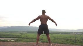 Συναρπαστική στιγμή του τεντώματος οικοδόμων σωμάτων αφροαμερικάνων στην αιχμή βουνών κατά τη διάρκεια της υπαίθριας κατάρτισης π απόθεμα βίντεο