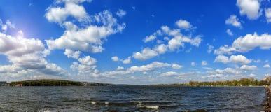 Συναρπαστικό τοπίο πολλά χνουδωτά σύννεφα στο μπλε ουρανό πέρα από το νερό ταραχώδης αστική λίμνη Στοκ Εικόνες