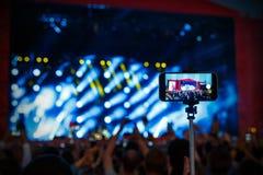 Συναυλία βράχου πυροβολισμού από το smartphone στο ραβδί selfie στοκ εικόνες με δικαίωμα ελεύθερης χρήσης