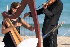 Συναυλία αρπών και βιολιών στην παραλία για τη ημέρα γάμου στοκ εικόνα με δικαίωμα ελεύθερης χρήσης