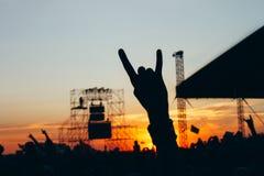 Συναυλία βράχου, σκιαγραφίες των ευτυχών ανθρώπων που αυξάνουν επάνω στα χέρια στοκ φωτογραφία με δικαίωμα ελεύθερης χρήσης