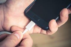 Συνδέοντας έξω ένα άσπρο USB καλωδιακό με ένα μαύρο κινητό τηλέφωνο, Holded από τα αρσενικά χέρια Στοκ Εικόνα
