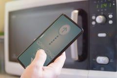 Συνδέοντας φούρνος μικροκυμάτων με το έξυπνο τηλέφωνο στοκ εικόνες με δικαίωμα ελεύθερης χρήσης