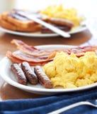 Συνδέσεις λουκάνικων με τα ανακατωμένα αυγά και το μπέϊκον στοκ εικόνες
