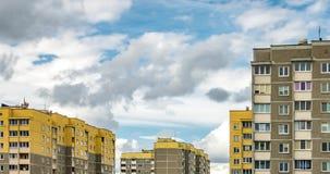 Συνδετήρας χρονικού σφάλματος των άσπρων χνουδωτών κυλώντας σύννεφων στα πλαίσια των κίτρινων multi-storey πολυκατοικιών απόθεμα βίντεο