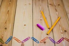Συνδετήρες εγγράφου, μολύβι, γόμα σε ένα ξύλινο υπόβαθρο στοκ εικόνα με δικαίωμα ελεύθερης χρήσης