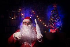 Συνεδρίαση Άγιου Βασίλη στην πολυθρόνα στο δωμάτιο που διακοσμείται για τα Χριστούγεννα Εκλεκτική εστίαση στοκ εικόνες