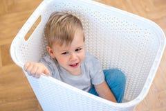 Συνεδρίαση αγοριών δύο ετών παιδιών σε ένα καλάθι πλυντηρίων και παιχνίδι στοκ εικόνα