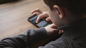 Συνεδρίαση αγοριών εφήβων από το παράθυρο σε έναν καφέ με ένα smartphone στα χέρια του Επικοινωνία στα κοινωνικά δίκτυα Παιχνίδια απόθεμα βίντεο