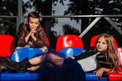 Συνεδρίαση αγοριών και κοριτσιών παιδιών στις πλαστικές καρέκλες σχολικών εξεδρών επισήμων Στοκ Εικόνες