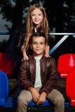 Συνεδρίαση αγοριών και κοριτσιών παιδιών στις πλαστικές καρέκλες σχολικών εξεδρών επισήμων Στοκ φωτογραφία με δικαίωμα ελεύθερης χρήσης