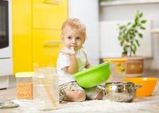 Συνεδρίαση αγοριών παιδιών στο πάτωμα κουζινών και παιχνίδι με το αλεύρι Στοκ Φωτογραφίες