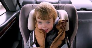 Συνεδρίαση αγοριών σε ένα αυτοκίνητο στην καρέκλα ασφάλειας απόθεμα βίντεο