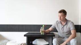 Συνεδρίαση ατόμων και σκέψη έχοντας το ποτό και κοιτάζοντας από το παράθυρο απόθεμα βίντεο