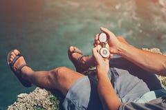 Συνεδρίαση ατόμων με την πυξίδα επάνω από τον ωκεανό στον απότομο βράχο Στοκ Φωτογραφίες