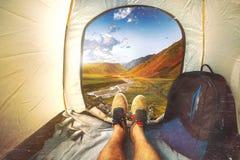 Συνεδρίαση ατόμων οδοιπόρων σε μια σκηνή τουριστών από τη θέα βουνού με τις γρατσουνιές Έννοια διακοπών διακοπών Άποψη των ποδιών Στοκ Εικόνες
