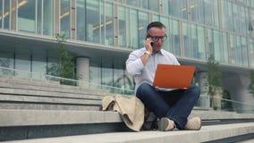 Συνεδρίαση ατόμων στα σκαλοπάτια και εργασία στο lap-top απόθεμα βίντεο