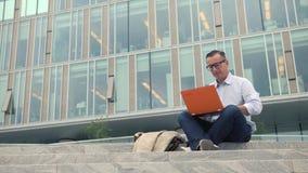 Συνεδρίαση ατόμων στα σκαλοπάτια και εργασία στο lap-top φιλμ μικρού μήκους