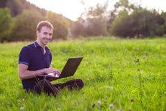 Συνεδρίαση ατόμων στην πράσινη χλόη με το lap-top και την εργασία Στοκ Φωτογραφία