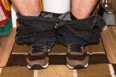 Συνεδρίαση ατόμων στην τουαλέτα με τα εσώρουχά του κάτω στοκ φωτογραφία
