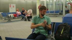 Συνεδρίαση ατόμων στη αίθουσα αναμονής, τον αερολιμένα ή το σιδηροδρομικό σταθμό, που ελέγχουν το χρόνο στο τηλέφωνο φιλμ μικρού μήκους
