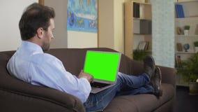Συνεδρίαση ατόμων στον αγαπημένο κινηματογράφο καναπέδων και προσοχής στο lap-top με την πράσινη οθόνη απόθεμα βίντεο