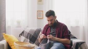 Συνεδρίαση ατόμων στον καναπέ και πλέξιμο στο άνετο σπίτι απόθεμα βίντεο