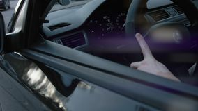 Συνεδρίαση ατόμων στο αυτοκίνητό του, χέρι στο τιμόνι, που εξετάζει τη κάμερα μέσω του δευτερεύοντος καθρέφτη κίνηση αργή απόθεμα βίντεο
