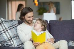 Συνεδρίαση βιβλίων ανάγνωσης πατέρων και γιων στον καναπέ στο σπίτι Στοκ εικόνα με δικαίωμα ελεύθερης χρήσης