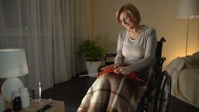 Συνεδρίαση γιαγιάδων στην αναπηρική καρέκλα πλέκοντας ένδυμα, που σκέφτεται για το εγγόνι φιλμ μικρού μήκους