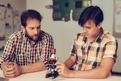Συνεδρίαση γιων κοντά στον πατέρα και χρησιμοποίηση του μικροσκοπίου στοκ φωτογραφίες με δικαίωμα ελεύθερης χρήσης