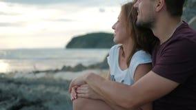 Συνεδρίαση γυναικών ανδρών στο αγκάλιασμα στην ακτή στο ηλιοβασίλεμα προσοχής πετρών φιλμ μικρού μήκους