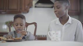 Συνεδρίαση γυναικών αφροαμερικάνων με την λίγος γιος από τον πίνακα στην κουζίνα Σχέση mom και γιος Μια ευτυχής οικογένεια απόθεμα βίντεο