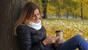 Συνεδρίαση γυναικών με την πίσω στο δέντρο στα κίτρινα φύλλα φθινοπώρου, χρήσεις Smartphone στοκ εικόνες