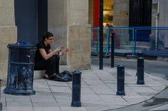 Συνεδρίαση γυναικών με το τηλέφωνο κυττάρων σε μια οδό στο Μπορντώ, Γαλλία, το Σεπτέμβριο του 2013 στοκ εικόνα με δικαίωμα ελεύθερης χρήσης