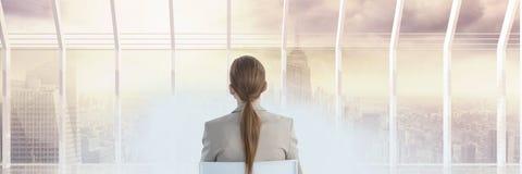 Συνεδρίαση γυναικών που εξετάζει έξω παράθυρο τον ορίζοντα με τον καπνό στο μέτωπο Στοκ Φωτογραφία