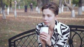 Συνεδρίαση γυναικών σε έναν πάγκο σε ένα πάρκο, έναν καφέ χαλάρωσης και κατανάλωσης απόθεμα βίντεο