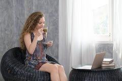 Συνεδρίαση γυναικών στην καρέκλα για να πιει τον καφέ στοκ εικόνες με δικαίωμα ελεύθερης χρήσης